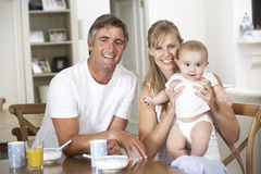 Family With Baby Having Breakfast In Kitchen Together Royalty Free Stock Photos