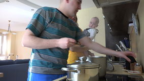 Family with baby prepare dinner in kitchen. Mom taste soup spoon stock footage