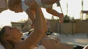 Family with baby resting on the loungers by the pool Royalty Free Stock Images