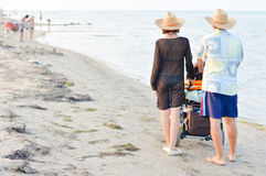 Family with baby stroller walking on sandy beach Royalty Free Stock Photo