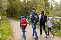Family with backpacks hiking or walking in woods stock image