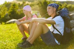 Family with backpacks resting outdoor. Adventure, travel, tourism concept Stock Photography