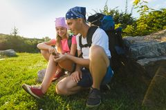 Man and girl with backpack resting and looking at compass Royalty Free Stock Image