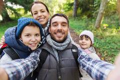 Family with backpacks taking selfie and hiking. Technology, travel, tourism, hike and people concept - happy family with backpacks taking selfie and hiking royalty free stock photo