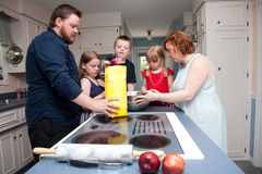 Family baking apple pie. A family of five baking apple pie in kitchen Stock Photos