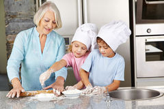 Family baking christmas cookies in kitchen. Family with grandmother and children baking christmas cookies in kitchen Stock Photography