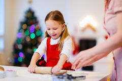 Family baking on Christmas eve. Family of mother and daughter baking gingerbread cookies at home on Christmas eve Royalty Free Stock Photo