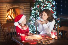 Family baking at Christmas. Mother and child bake. Mother and daughter baking Christmas cookies at fire place and decorated tree. Mom and child bake Xmas sweets Stock Image