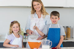 Family baking cookies at counter top. Portrait of mother with son and daughter baking cookies at counter top in kitchen stock photo