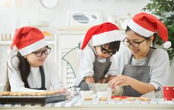 Family baking cookies in the kitchen. Asian Family wear Santa hats and glasses are preparing the dough for baking cookies in the kitchen. New year and Christmas stock photography