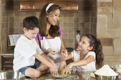 Family Baking and Eating Cookies In Kitchen. An attractive smiling family of mother, and two children, boy, girl, son, daughter baking and eating fresh chocolate royalty free stock photography