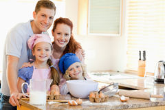 Family with baking ingredients behind the kitchen counter Stock Image