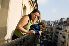 Family on balcony. Mother and her son on balcony looking at city life Royalty Free Stock Photo