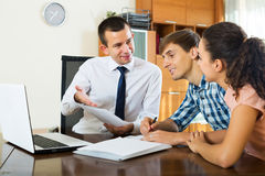 Family and banking agent discussing. Smiling young family couple and positive banking agent discussing possibility of mortgage Royalty Free Stock Images