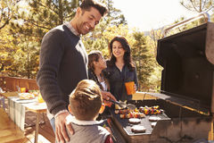 Family barbecuing on a deck in the forest Stock Images