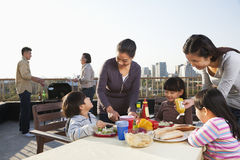 Family barbeque party, sitting at the table Royalty Free Stock Photo