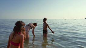 Family bathe in the sea. The boy stumbles in the water a funny video. Family holiday in summer at sea Royalty Free Stock Images