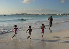 Family on a Beach. Father and his children are playing on Carlisle Bay in Bridgetown, Barbados stock photos
