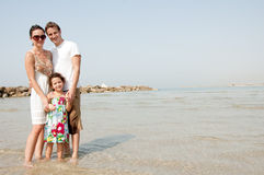 Family on the beach. Young family standing with young daughter in the beach stock image