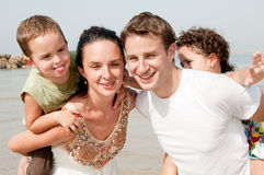 Family in the beach. Parents with children sitting on the shoulders royalty free stock photos