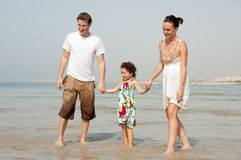 Family in the beach. Father mother and daughter playing in the beach royalty free stock photo