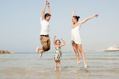 Family in the beach. Father mother and daughter playing and jumping in the beach stock photography