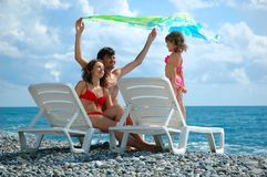 Family on beach. With flying pareo Stock Photos