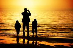 Family on the beach. Silhouettes of father and two sons by the ocean looking to the sunset Royalty Free Stock Photos