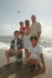 Family at the Beach. A family portrait. An american family on the shore of a beach with seagulls behind them stock image