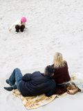 Family at beach. Parents sitting on a blanket, watching their child play in the sand at a beach Royalty Free Stock Photos