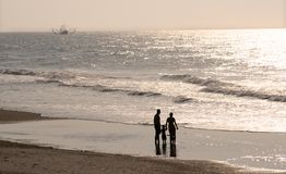 Family on the beach. A family of three gazing at the ocean and  a shrimp boat in the early morning light Royalty Free Stock Photos