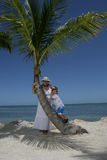 Family on beach. A woman and her son on their vacation under a palm tree on the beach Royalty Free Stock Photography