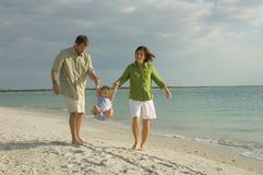 Family at beach. A young happy family playing on the beach Royalty Free Stock Photography