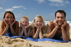 Family at the beach. Father, mother, and two children lying on the beach, smiling at the camera Royalty Free Stock Photo