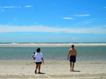 Family on beach. Rear view of couple with one child on sandy beach, sea in background Stock Image
