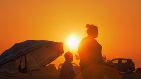 Family at the beach after bathing. View at sunset. Nea Kallikratia, Greece - August 12, 2017: family at the beach. Man is drying with towel, while child getting stock footage