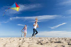 Family on the Beach Flting a Kite. Family playing together on the beach. Kite is above their heads Royalty Free Stock Image