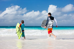 Family beach fun. Father and son running towards ocean with boogie boards Royalty Free Stock Photos