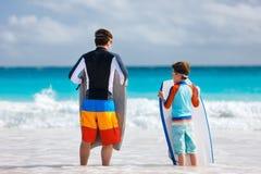 Family beach fun. Father and son at beach facing ocean with boogie boards Stock Photos