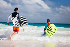 Family beach fun. Father and son running towards ocean with boogie boards Stock Photography