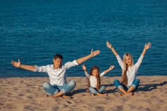 Family at the beach. lotus posture. hands up Royalty Free Stock Image
