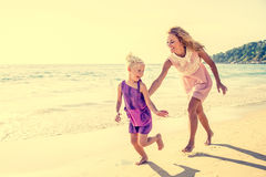 Family on the beach. Mom and daughter running on the beach - Family moments, beautiful young mother trying to catch her daughter, having fun and enjoying summer Stock Photo