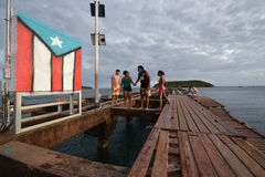 Family at the Beach next to flag in Vieques, Puerto Rico Stock Photos