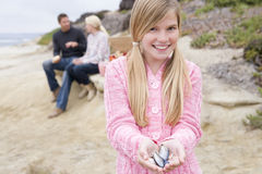 Family at beach with picnic and girl with shell Royalty Free Stock Photos