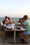 Family in the beach restaurant. At sunset stock photo