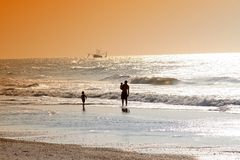 Family on beach at sunset. Silhouette of father on beach with two children at sunset watching shrimp boat at sea Royalty Free Stock Photography