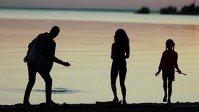 Family on the beach at sunset. Silhouettes of men, women and girls stock footage