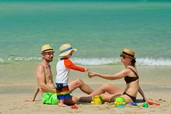 Family on beach. Toddler playing with mother and father. Family on beach. Two year old toddler boy playing with beach toys with mother and father on beach Royalty Free Stock Photo