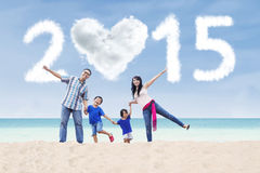 Family at beach under cloud of 2015 Stock Images