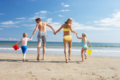 Family on beach vacation. Running towards sea royalty free stock image